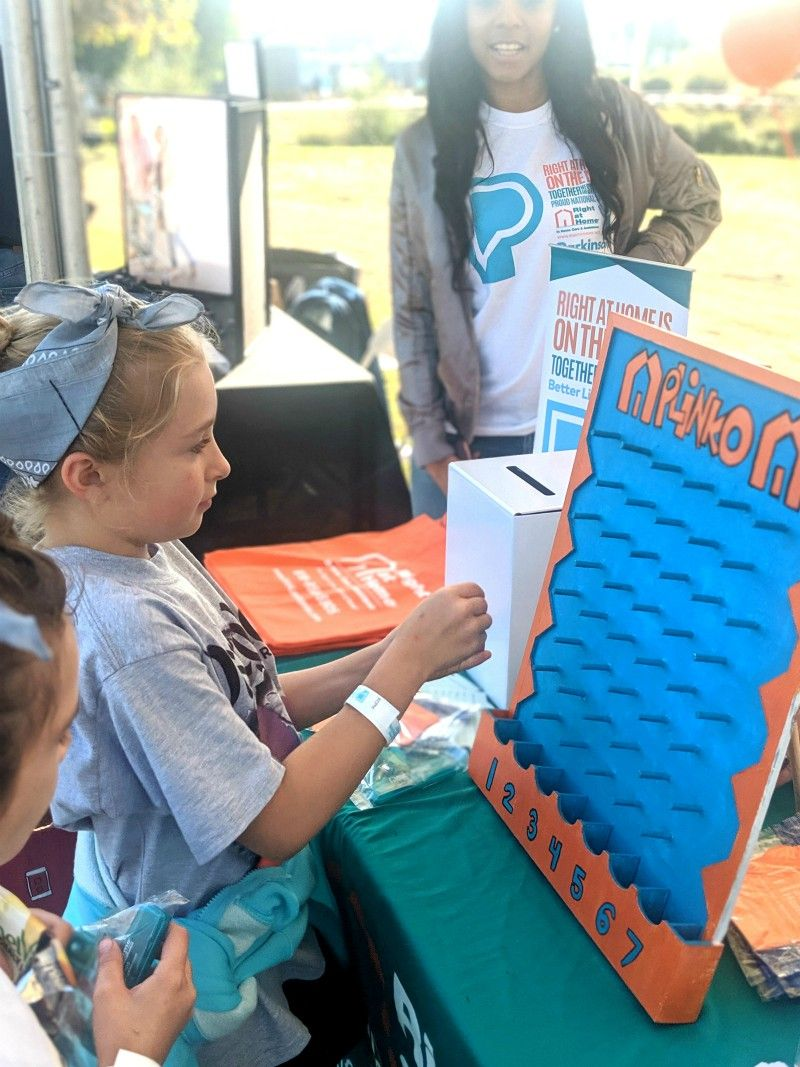 Girl playing Right at Home Plinko at Moving Day event