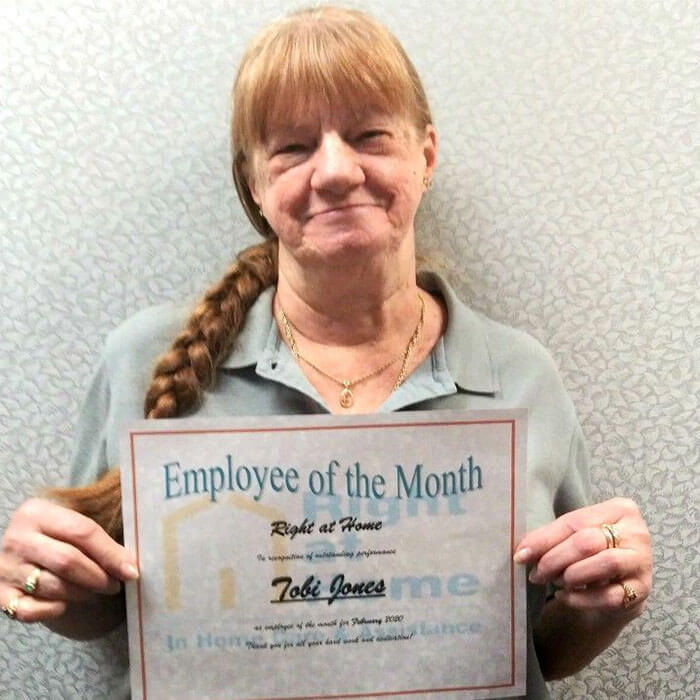 photo of caregiver holding employee of the month certificate