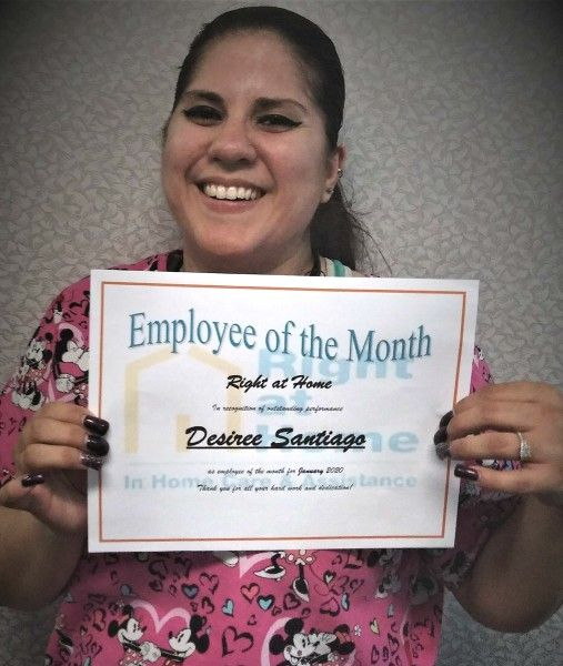 Desiree holding Caregiver of the Month certificate