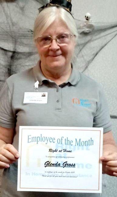 Glenda Gross holding an Employee of the Month certificate