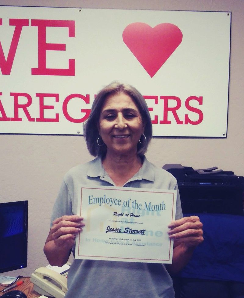 Jessie S. holding Employee of the Month certificate and standing in front of sign that says, 'We Love Our Caregivers'