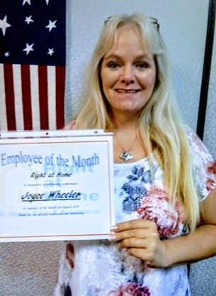 Joyce holding Caregiver of the Month certificate in front of American Flag hanging vertical on wall in background