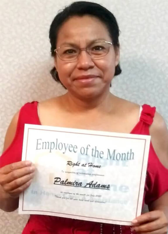 Profile photo of Palmira A. holding employee of the month certificate