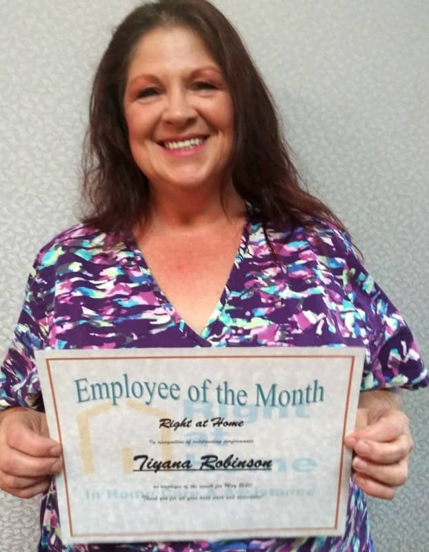 profile photo of Tiyanna holding Employee of the Month certificate