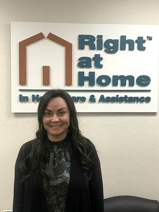 Destiny Rodriguez in front of Right at Home sign in the office