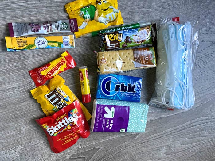 various snacks, candy and items including a mask for caregiver care packages