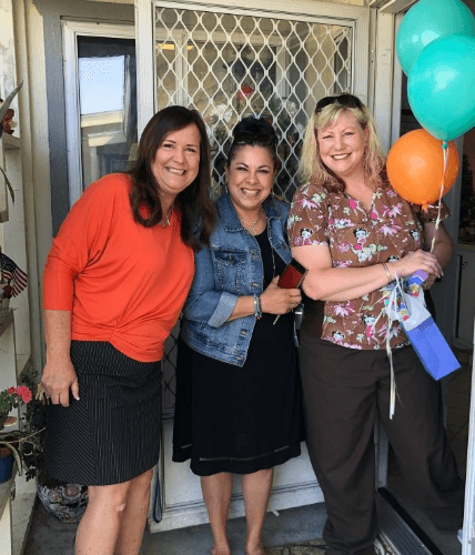 Pauline awarded Caregiver of the Year holding balloons and gift bag next two to owner Lorette Oliver and Mary Peterson in front of a door to a home.