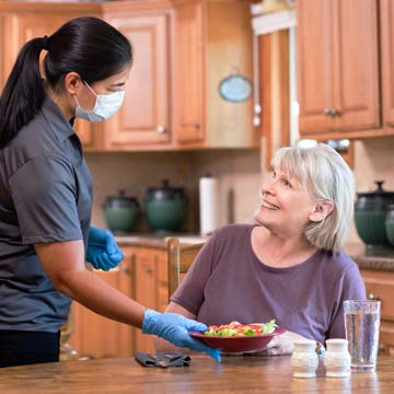 Caregiver Serving a Custom-Cooked Meal to a Client