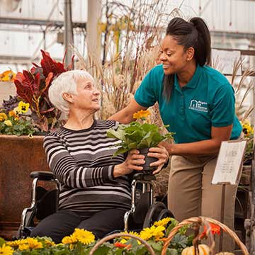 Caregiver with Client in Wheelchair Shopping at Garden Center